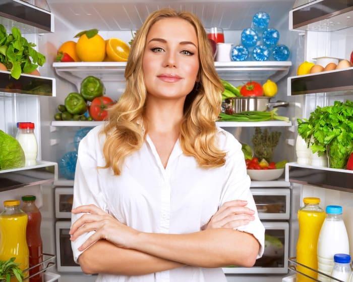 Portrait of cute serious female standing near open fridge full o