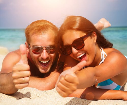 Happy Couple in Sunglasses having fun on the Beach. Summer Vacat