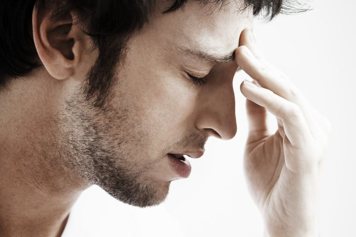 Side view of young man with headache touching forehead on white