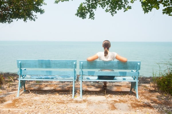 Young woman sitting on bench facing the sea in Thailand