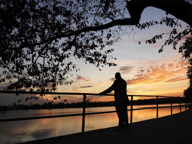 African-American man standing by water at sunset in Washington,