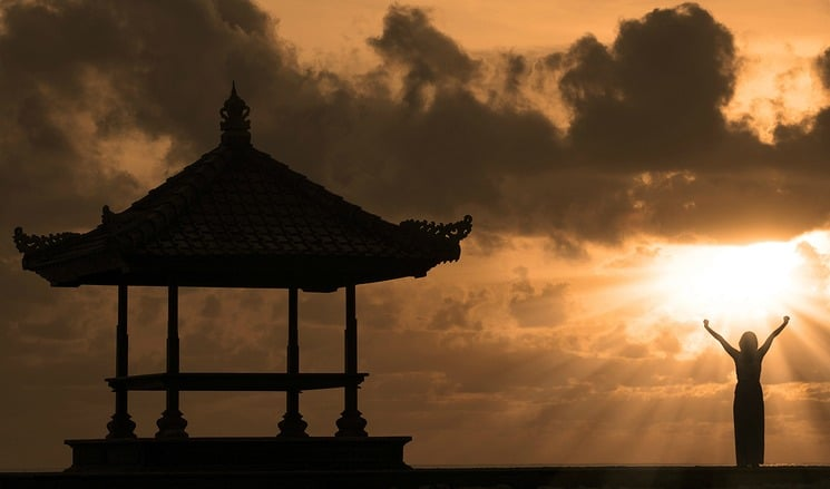 Silhouette of woman and outdoor pavilion during sunset at Bali beach Indonesia