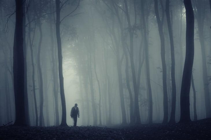 Man in a dark forest with fog